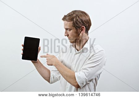 Young Adult Man in White Shirt Holds a Tablet and Points to It With His Finger