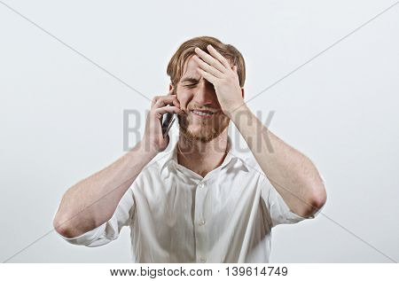Young Adult Man in White Shirt Listening to His Phone, Holding His Head in Hands, Receiving Bad News