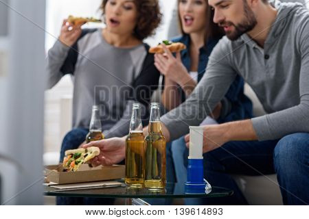 Pause in game. Close up of bottles of beer on the table with friends eating pizza, smiling, chatting and watching tv in background