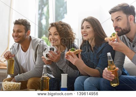 Pizza time. Laughing group of smiling young friends sitting on sofa and watching television, eating pizza with bottles of beer