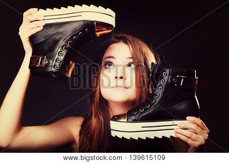 Women loves shoes teenage fashion concept - female model teenager girl holding casual stylish sneakers on black