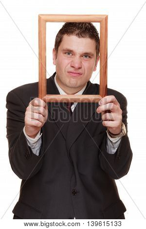 Nerdy funny business man guy framing his face with wooden empty picture frame isolated on white background