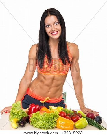 Portrait of slim fitness cheerful girl tanding near table with set of fruit and vegetables over white background. Healthy eating, diet, fitness, weight lose concept.
