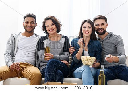 Wonderful evening with friends. Group of friends sitting in sofa watching sport game on tv with beer and popcorn