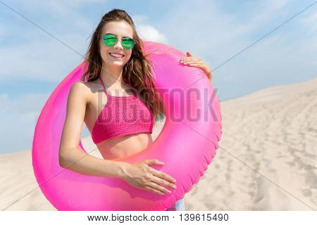 Playful mood. Cheerful young woman holding inflatable ring and smiling while standing on the beach