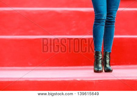 Autumn fashion outfit. Fashionable woman long legs in denim pants black stylish high heels shoes outdoor on red steps