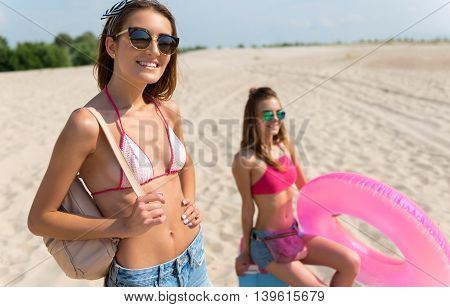 Sunny mood. Positive beautiful pleasant woman holding bag on the shoulder and having rest with her friend on the beach