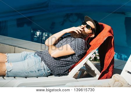 young handsome bearded man with long beard in sun glasses on face laying on beach chair at swimming pool with blue water sunny summer vacation