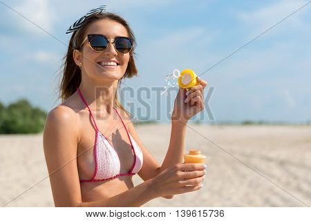 Childish fun. Positive beautiful delighted woman blowing soap bubbles and smiling while resting on the beach