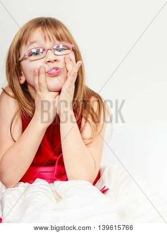 Play and fun. Charming little girl making funny crazy face. Smiling lovely cute female child wearing glasses. Positive facial emotion.