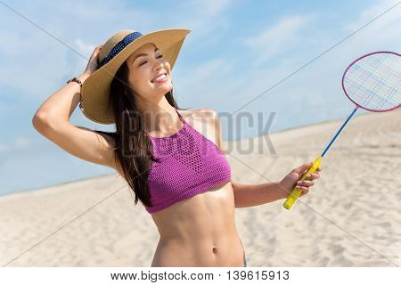 Activate your body. Positive delighted beautiful woman holding rocket and playing badminton while resting on the beach