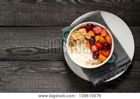 Concept of diet and healthy eating. Cereal flakes with yogurt strawberries apricots cherries in a bowl on old wooden table. Top view space for text
