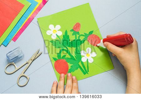 The child making the applique of paper on a summer theme with strawberries. The idea for children's creativity an art project made of paper. Sheets of colored paper glue scissors marker pen