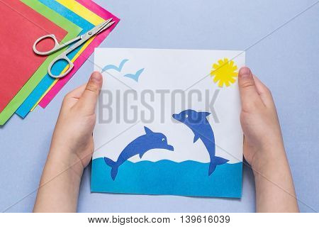 Paper applique is made by the child on a sea theme. The idea for children's creativity an art project made of paper. Sheets of colored paper glue scissors. Children's hands holding a picture