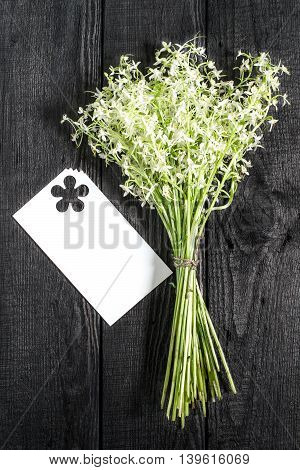 Delicate bouquet of wild orchids also known as Lesser Butterfly Orchid (Platanthera bifolia) and card for text on a dark wooden background