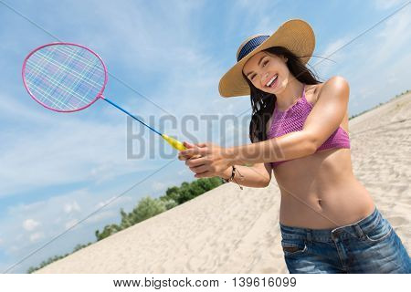 Great serve. Beautiful sporty joyful woman holding rocket and playing badminton while having fun on the beach