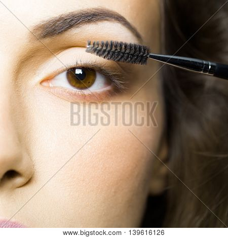 young sexy woman with soft skin and beautiful eyebrow on pretty face and brown eye holding fashionable makeup mascara brush near eyelashes closeup