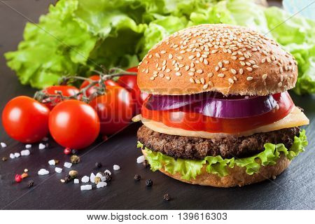Homemade cheeseburger with beef patties, fresh salad, tomatoes and onion on seasame buns, served on black slate table.