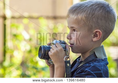 Cute little happy boy with vintage photo camera outdoors