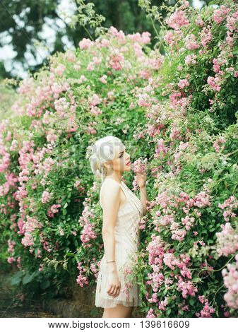 Young woman with pretty face blonde hair in beautiful vogue cream-colored dress posing near rose bush in pink blossom background outdoor