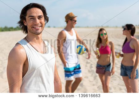 Nice company. Cheerful handsome man smiling and standing on the beach while resting with his friends who is standing in the background