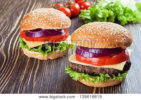 Two homemade cheeseburgers with beef patties , fresh salad, tomatoes and onion on seasame buns, served on brown wooden table.