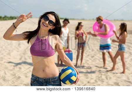On the emotional wave. Joyful delighted smiling woman holding ball for volleyball and smiling while resting on the beach with her friends