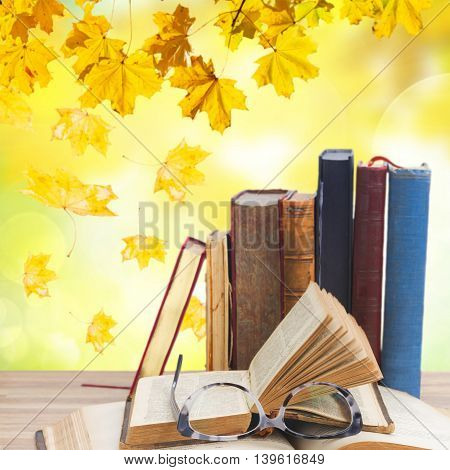 Books and glasses close up on wooden table desktop , fall leaves in background