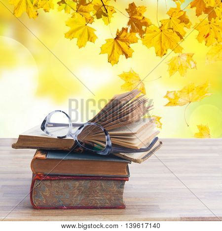 Stack of old books and glasses on wooden table desktop, fall leaves in background