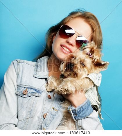 teenage girl with Yorkshire Terrier over blue background