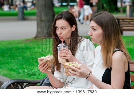 Caucasian women eating hamburger fast food sandwich on the street outdoors. Active girls hungry and eating street food after long walk
