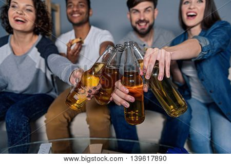 Celebration of winning favourites football team. Cropped shot of group of friend toasting with beer bottles, isolated on gray background