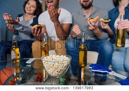 We are here for good time. Close up of plate of popcorn standing on table with beer bottles and football fans sitting on couch in gray background