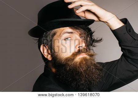 handsome bearded young man hipster or gentleman with long beard and mustache in stylish black retro hat on serious face in studio on grey background portrait