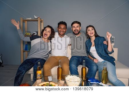 Let good times flow. Happy football fans celebrating victory of their team with beer and popcorn at home