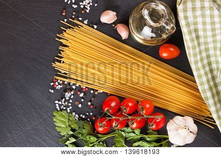 Pasta ingridients and spice on black slate surface. Top view.