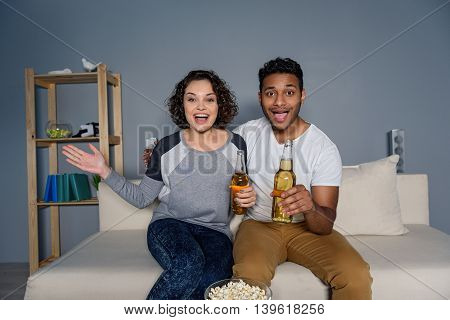 Incredible game. Beautiful couple cheering while watching football match on television, isolated on grey background