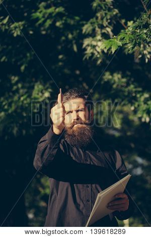 handsome sexy bearded young man hipster with long beard and mustache has stylish hair on serious hairy face sunny day outdoor holding note and pencil on green natural background