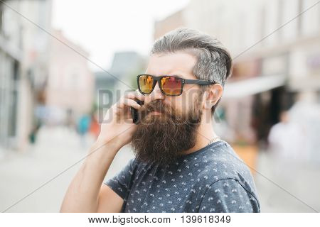 handsome sexy bearded young man hipster with long beard and mustache has stylish hair on serious hairy face in sun glasses speaking on mobile phone outdoor closeup