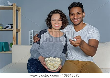 Long-awaited series. Happy couple watching tv at home sitting in comfortable couch in livingroom at home