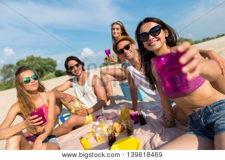 Cheers. Positive emotional smiling friends having a picnic while resting on the beach together
