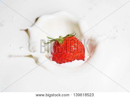 Strawberry splashing into milk isolated on white background