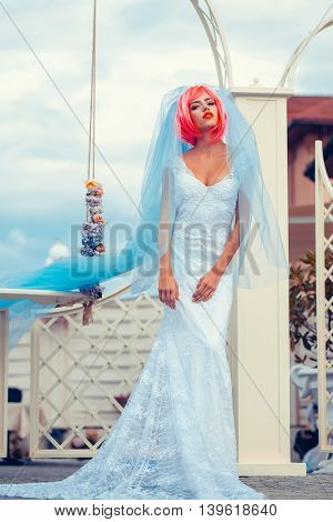 young woman with orange or pink hair and bright makeup on pretty face in white wedding dress and blue bride veil on natural cloudy sky background near floral swing