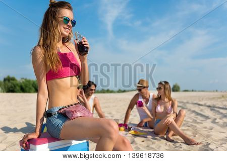 Just relax. Cheerful charming young woman drinking lemonade while her friends having picnic in the background
