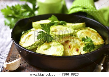 Fried Zucchini In A Skillet With Spicy Green Sauce.