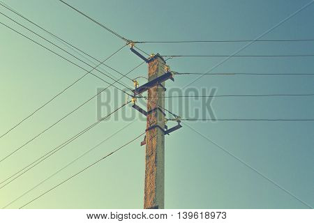 Electric pole with wires against the sky