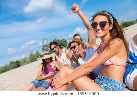 express your feelings. Cheerful smiling friends sitting on the sand and having fun while enjoying the picnic