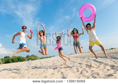 Overwhelmed with emotions. Cheerful delighted smiling friends jumping and feeling glad while resting on the beach