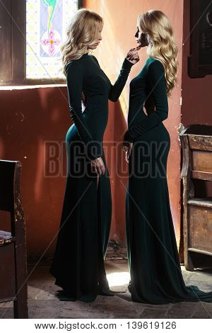 Two attractive women charming sisters twins with long blonde hair in green sexi dress posing opposite each other on background of old window indoor