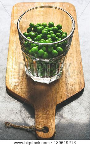 Raw green peas in a transparent glass on wooden board